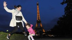 Lara and Mom at the Eiffel Tower by night. Lara is the world's youngest travel blogger.